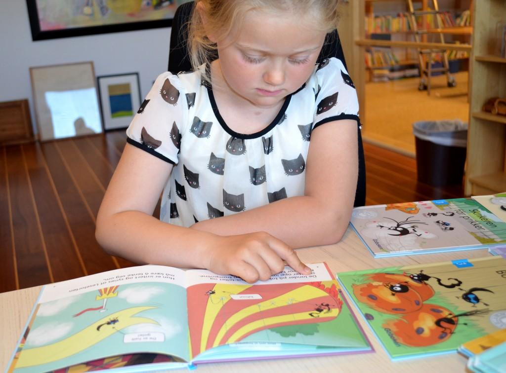 Pekfingret hjälper Astrid att få med alla bokstäverna när hon läser.